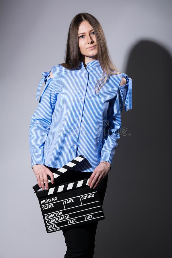 Young brown-haired woman with a movie cracker. Assistant director girl with long hair and striped shirt on a gray background royalty free stock photography
