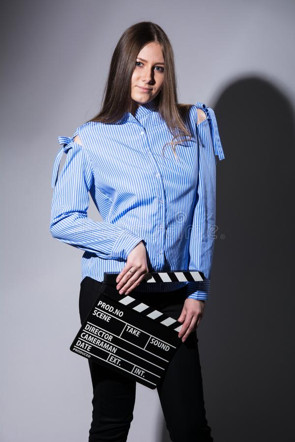 Young brown-haired woman with a movie cracker. Assistant director girl with long hair and striped shirt on a gray background royalty free stock photo