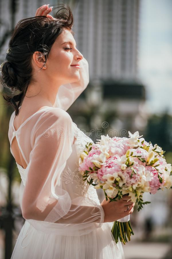Young brunette bride in a white dress with bouquet. Closeup portrait of a woman outdoor royalty free stock image