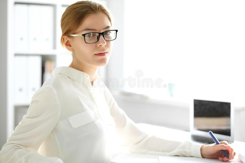 Young brunette business woman looks like a student girl working in office. Caucasian girl happy at work and too busy stock image
