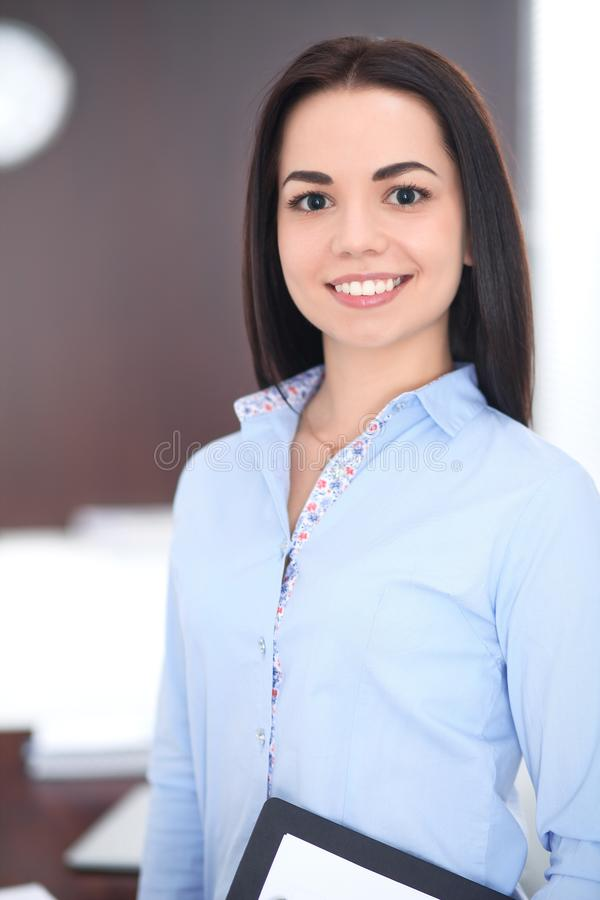 Young brunette business woman looks like a student girl working in office. Hispanic or latin american girl happy at work stock image