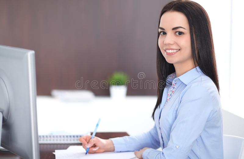 Young brunette business woman looks like a student girl working in office. Hispanic or latin american girl happy at work stock photography