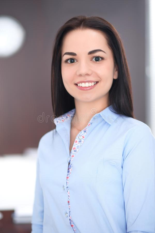Young brunette business woman looks like a student girl working in office. Hispanic or latin american girl happy at work royalty free stock image