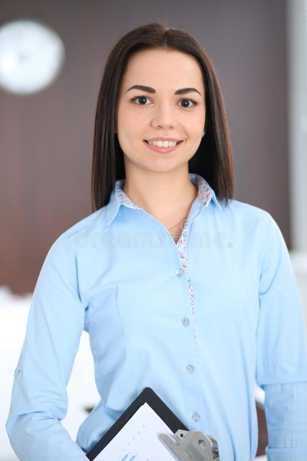 Young brunette business woman looks like a student girl working in office. Hispanic or latin american girl standing royalty free stock images