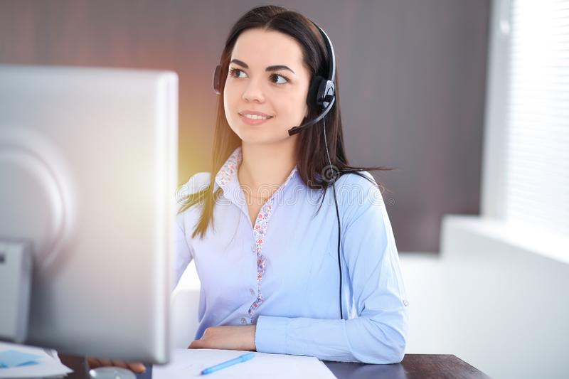 Young brunette business woman looks like a student girl working in office. Hispanic or latin american girl talking by stock photo