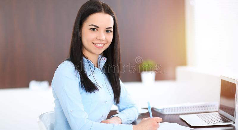 Young brunette business woman looks like a student girl working in office. Hispanic or latin american girl happy at work stock images