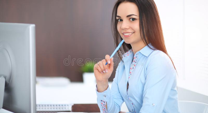 Young brunette business woman looks like a student girl working in office. Hispanic or latin american girl happy at work royalty free stock images