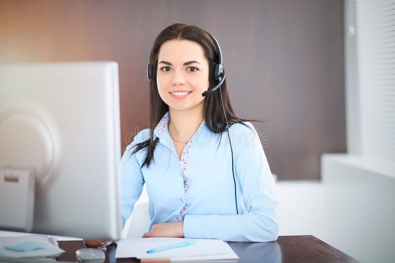 Young brunette business woman looks like a student girl working in office. Hispanic or latin american girl talking by. Headphones near pc royalty free stock images