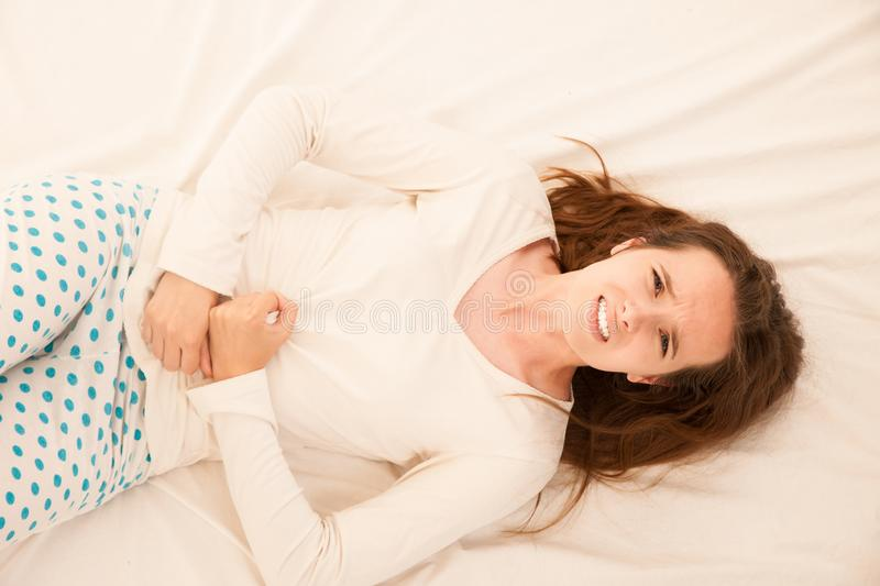 Young brunette caucasian woman wtih pain in her stomach menstrual cycle stock photos