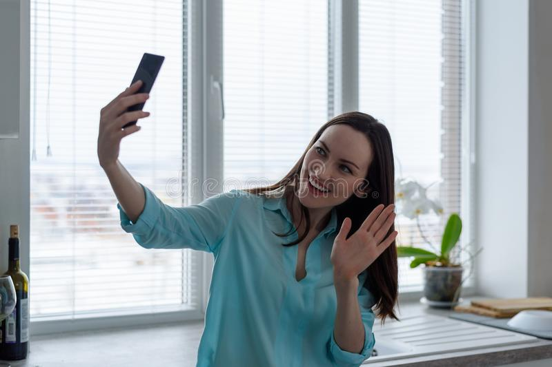 A young brunette communicates online through a smartphone in the kitchen, waving a greeting symbol royalty free stock photos