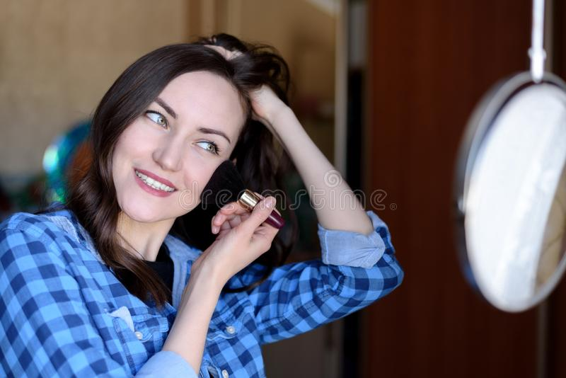 Young brunette corrects make-up at the round mirror in the bedroom stock image