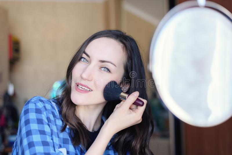 Young brunette corrects make-up at the round mirror in the bedroom stock photography