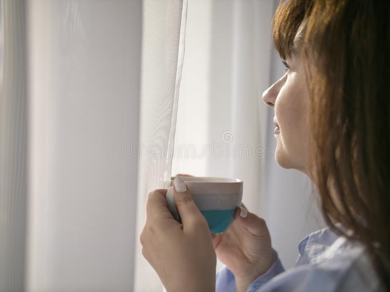 Young brunette with a cup of coffee looks out the window, close-up. Young brunette with a cup of coffee by the window, close-up royalty free stock photo