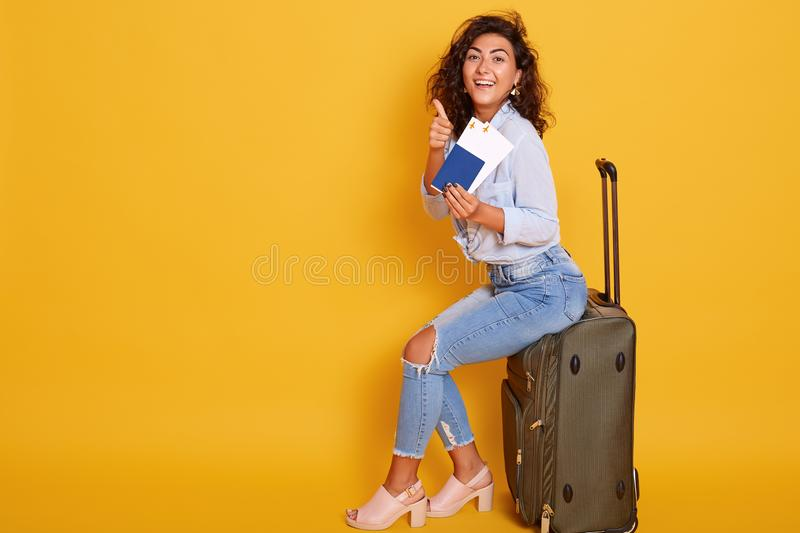 Young brunette curly woman sits on grey luggage bag in front of yellow background pointing with her index finger at ticket in her. Hand. Female wearing stylish stock photos