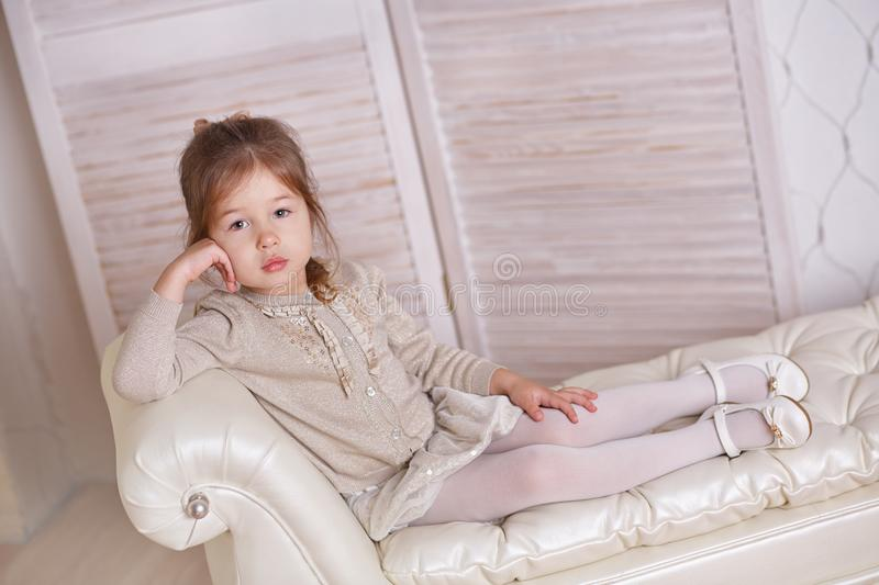 Young brunette dolly lady girl stylish dressed in white skirt midi petticoat and cardigan strap shoes smiling posing sitting in st. Udio on old style sofa couch royalty free stock image