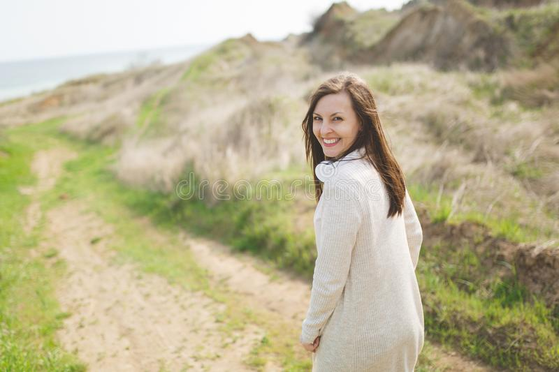 Young brunette emotional beautiful woman in light casual clothes walking along path standing in sunny weather in field. Near water on green background stock images