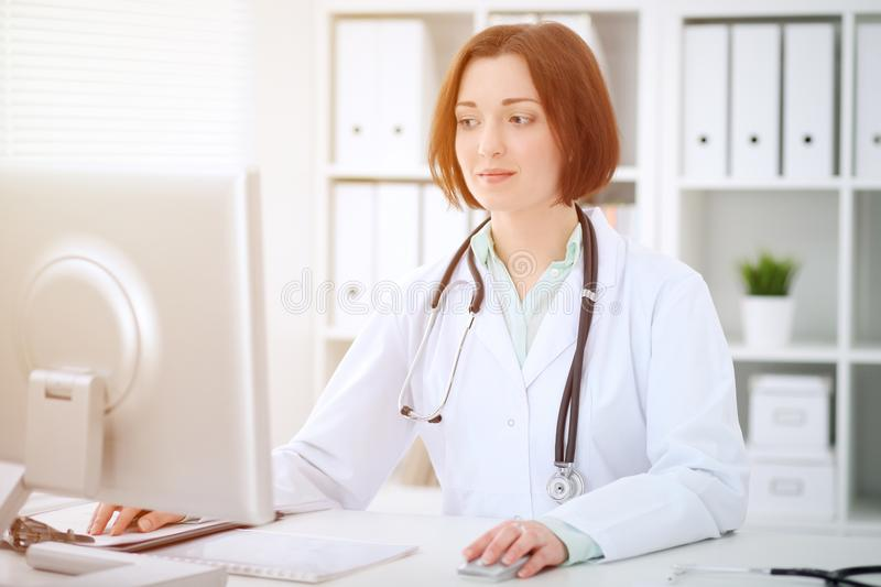 Young brunette female doctor sitting at the table and working with computer at hospital office royalty free stock image