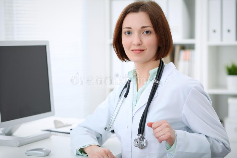 Young brunette female doctor sitting at the table and working with computer at hospital office stock photos