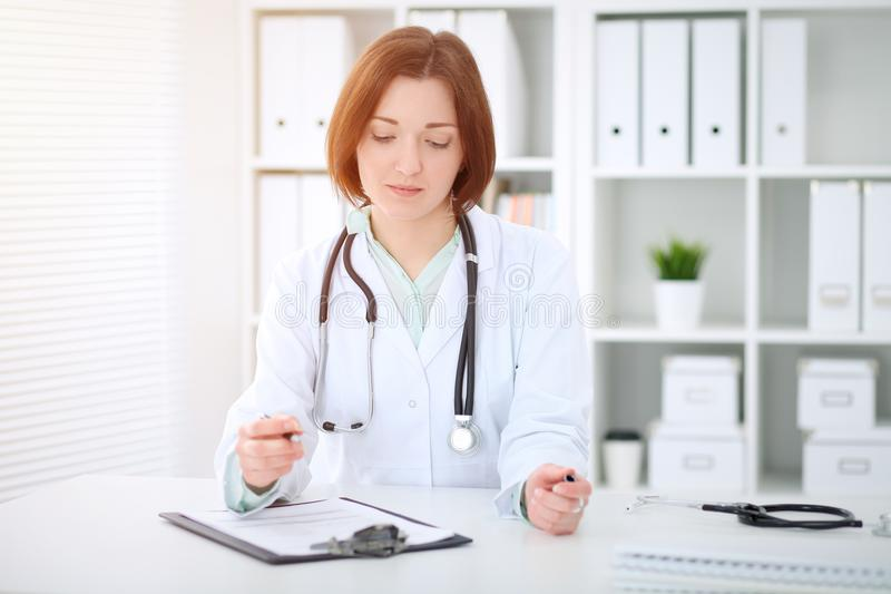 Young brunette female doctor sitting at the table and working at hospital office stock photos