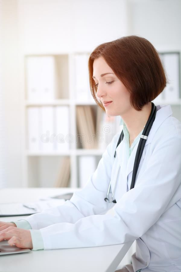 Mature Female Doctor Using Laptop While Working In Doctors Room Stock Photo