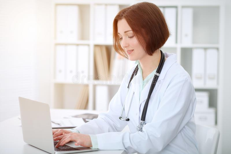 Young brunette female doctor typing on laptop comoputer while sitting at the table in hospital office. Health ca royalty free stock images