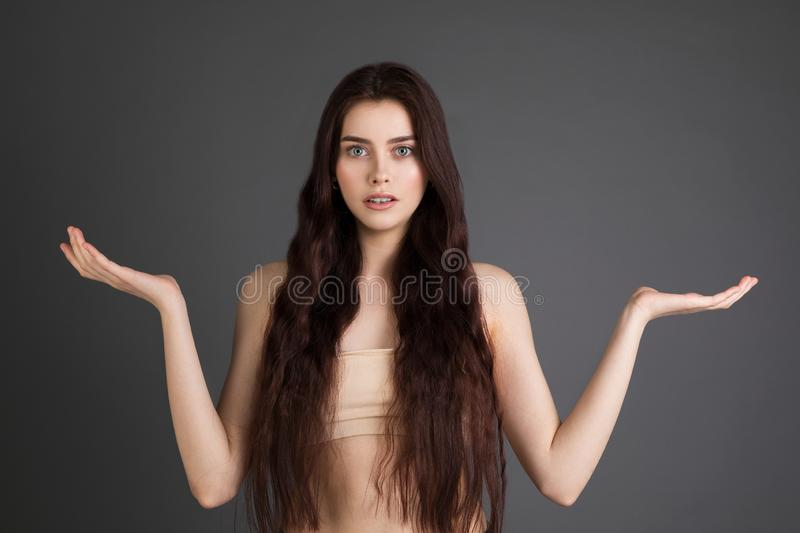 Young brunette girl with bare shoulders pointing hands on side to present a product royalty free stock photography