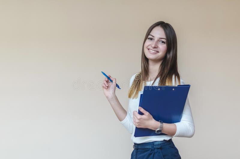 Young brunette girl with blue folder and pen on a light background royalty free stock image