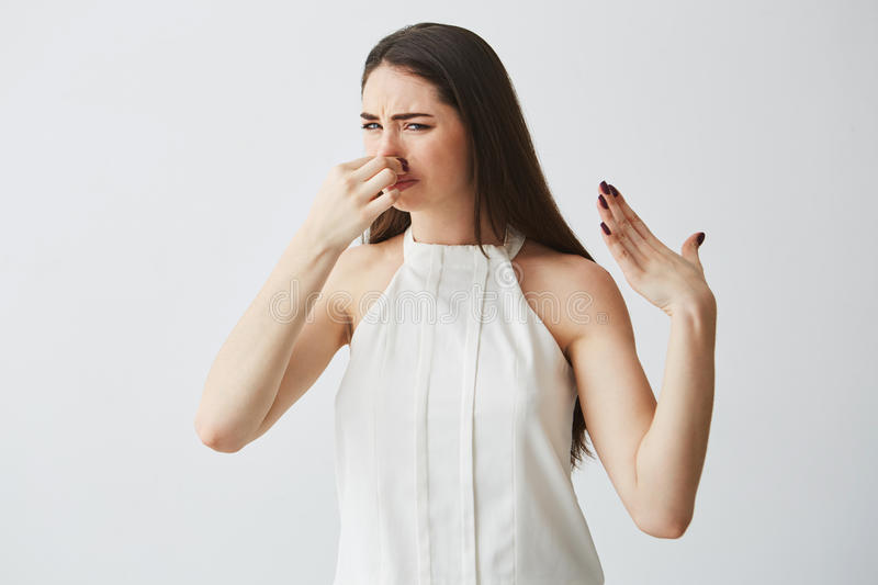 Young brunette girl closing covering nose over white background. Bad smell. royalty free stock photo