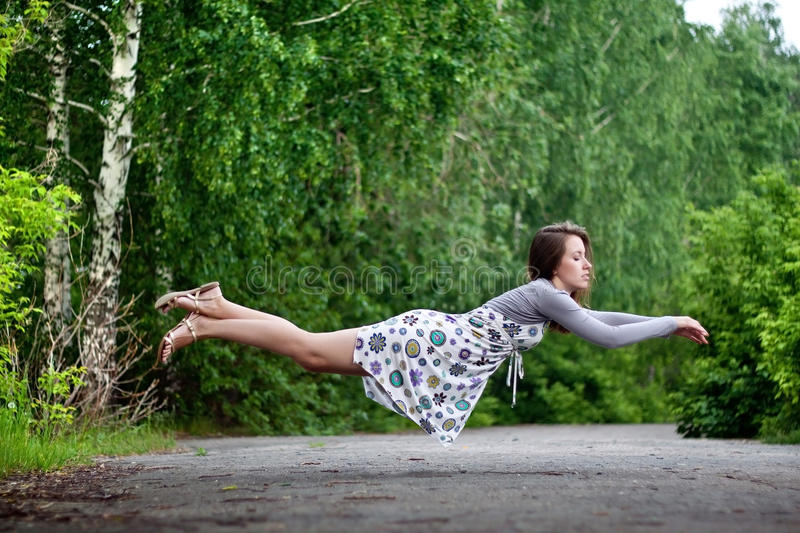 Young brunette girl in colorful dress levitating in the park royalty free stock photography