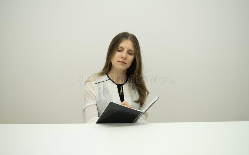 Young brunette girl with flowing hair is sitting at a table with a notebook in her hands royalty free stock image