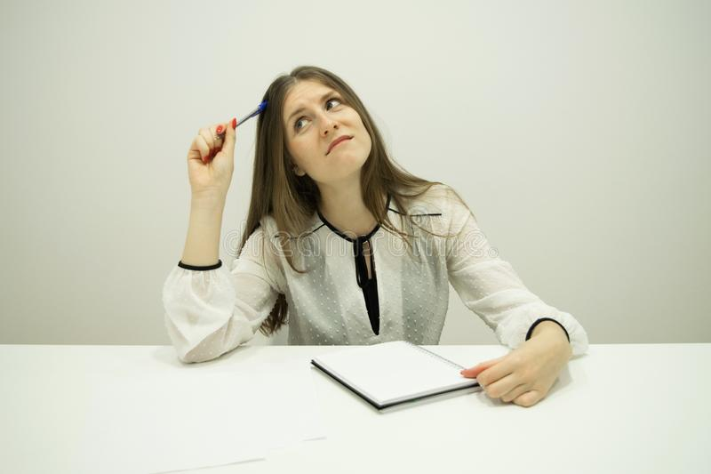young brunette girl with flowing hair is sitting at a table with a notepad on the table royalty free stock photo