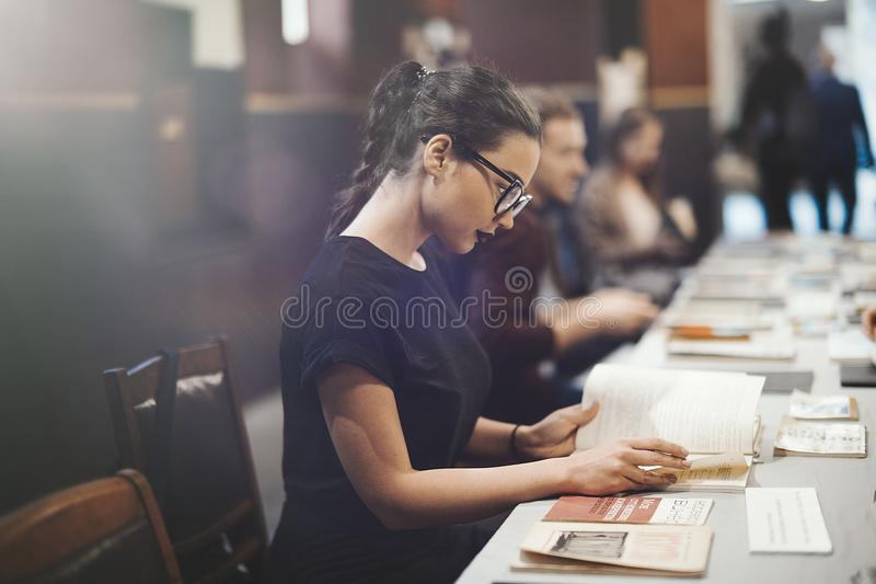 Young brunette girl with glasses and black lipstick reading book royalty free stock images