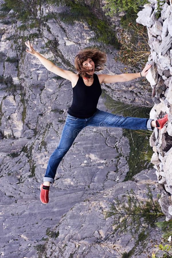 Young girl. Gray rock. Rest in mountains. Acrobat stock photo