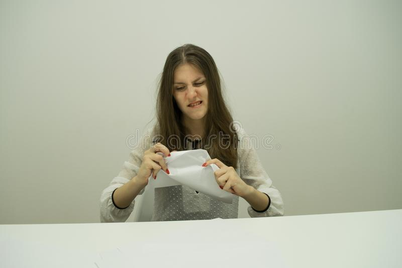 young brunette girl with her hair sits at a table with papers stock photography