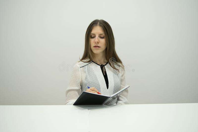 Young brunette girl with her hair straight sits at the table with a notebook in her hands royalty free stock photo