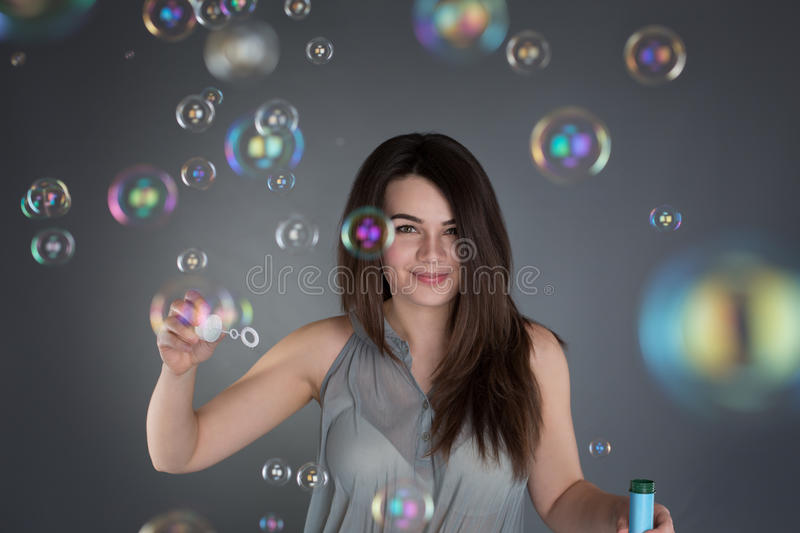 Young brunette girl inflating soap bubbles on the grey backgroun stock photos