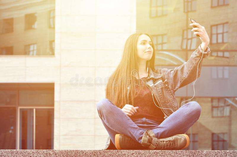 Young girl doing selfie on the background of an office building. Young brunette girl in jeans doing selfie on a smartphone on the background of an office stock photos