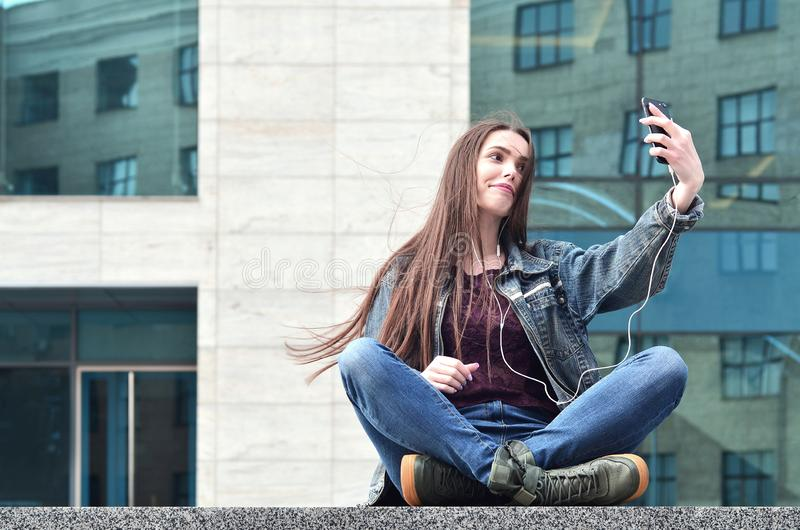 Young girl doing selfie on the background of an office building. Young brunette girl in jeans doing selfie on a smartphone on the background of an office royalty free stock images