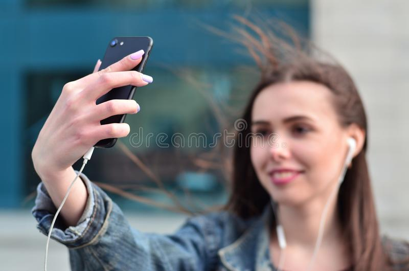Young girl doing selfie on the background of an office building. Young brunette girl in jeans doing selfie on a smartphone on the background of an office royalty free stock photo