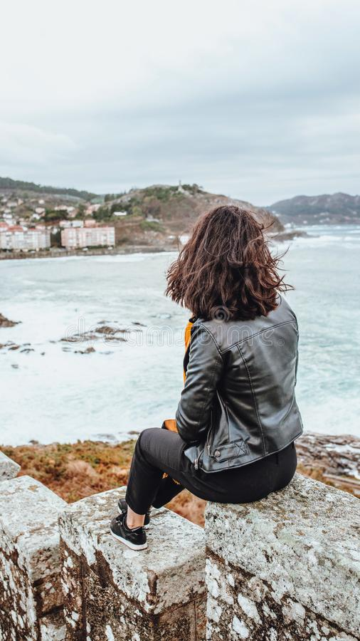 Young brunette girl looking at the sea royalty free stock image