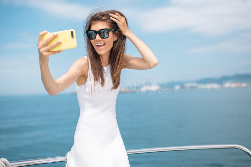 Young brunette girl making selfie using phone posing on luxury yacht. Young beautiful brunette girl in elegant white dress making selfie using smartphone on the royalty free stock image