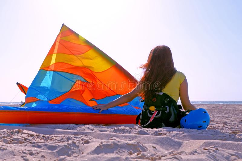 Young brunette girl with pancake hair in a T-shirt and equipment with a kite and helmet sitting resting on seashore royalty free stock image