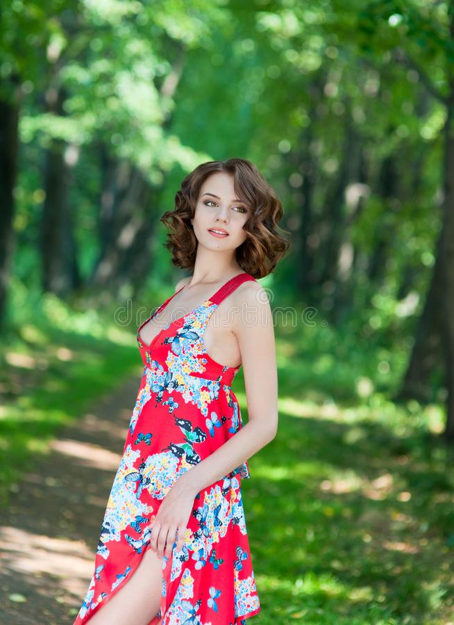 Young brunette girl in red dress posing on alley in summer park against trees stock photo