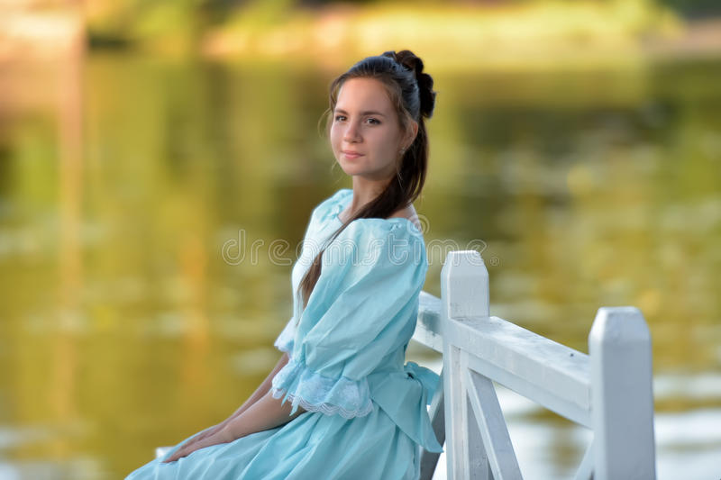 young brunette girl in retro vintage dress sitting stock image