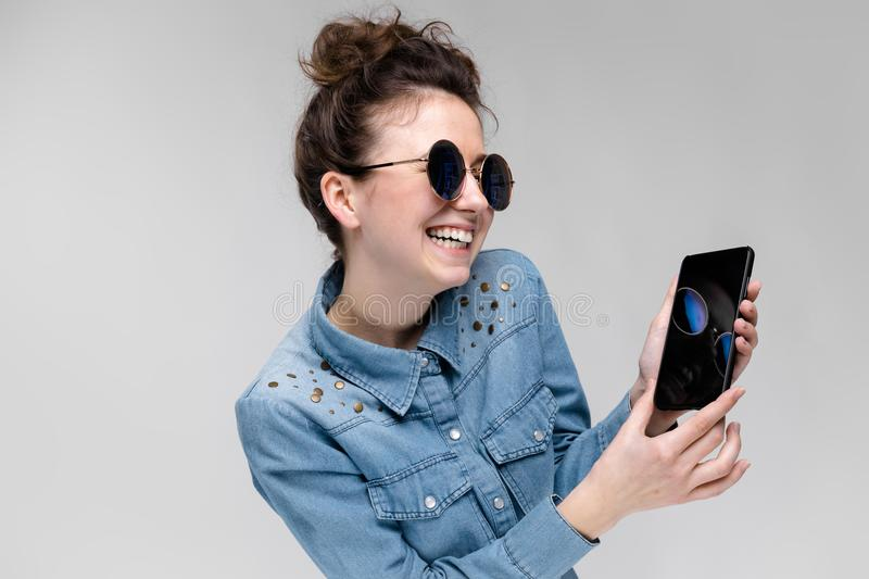 Young brunette girl in round glasses. Hairs are gathered in a bun. Girl with a black phone. The girl is looking at the stock photo