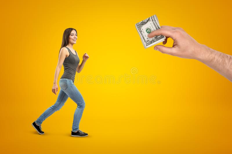 Young brunette girl wearing casual jeans and t-shirt going to male hand with money dollars on yellow background stock images