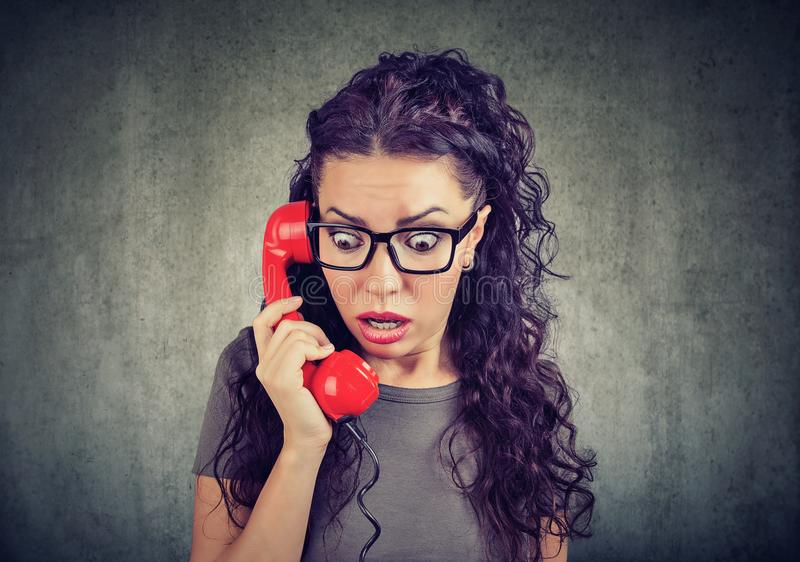 Shocked woman speaking on telephone stock photography