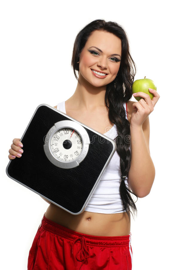 A young brunette with a green apple and scales. A young and happy brunette Caucasian woman in red shorts with a fresh green apple and weight scales. The image is royalty free stock image