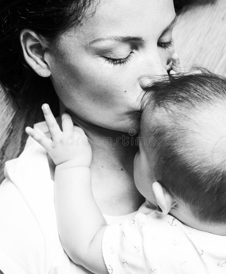 Young brunette happy mother holding toddler baby son, breast-feeding concept, lifestyle modern people stock photo