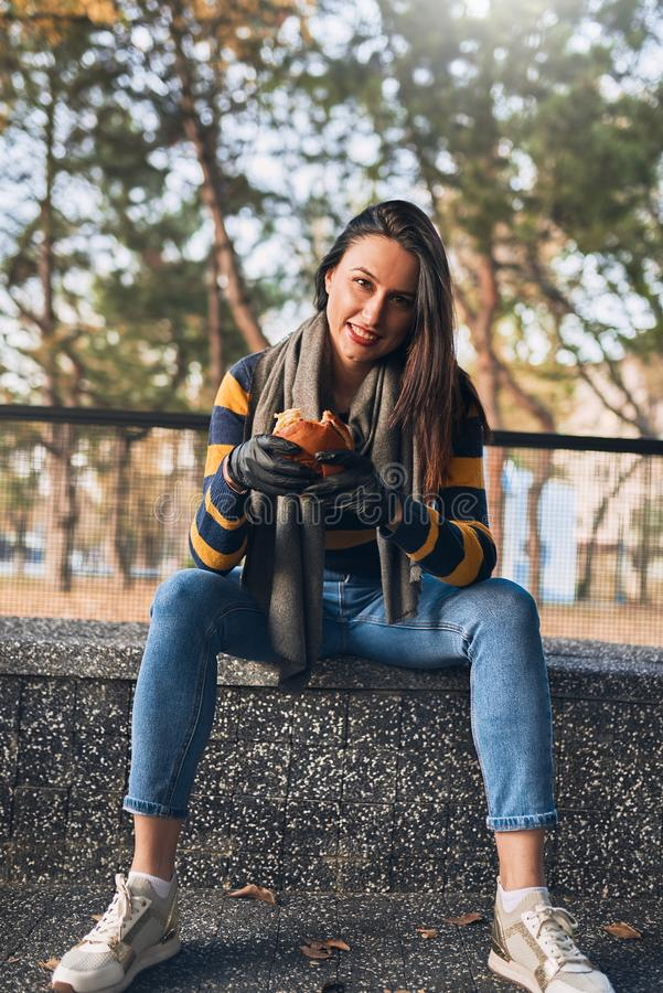 Young brunette hipster girl holding in hands fast food burger, unhealthy food. Hungry female smiling with grilled hamburger stock image